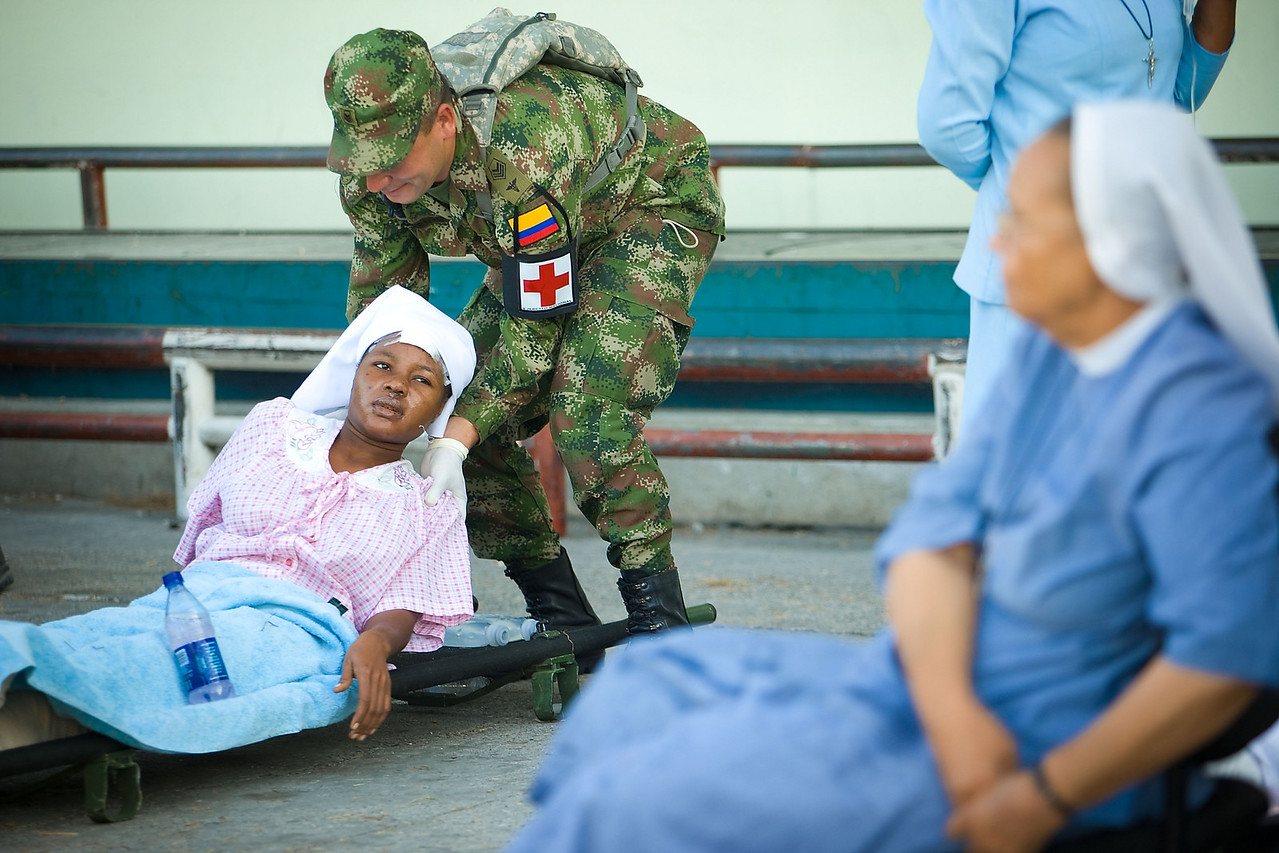 1/15/10 Port au Prince, Haiti  - Airport - Sister Elida Vixamar, cq, receives aid from members of the Columbian military. Sgt. Eto Bernal is at left. Vixamar and many of her Sisters were casualties of the earthquake. Several IMSuRT and DMAT teams from all over the country, roughly 300 people, arrived in Haiti on Friday afternoon. The supply cache had not yet arrived, and without a defined mission, it was unclear where the aid groups were to go immediately. For the evening, they plan to sleep outdoors at the embassy. Story by Stephen Smith/Globe Staff. Dina Rudick/Globe Staff.