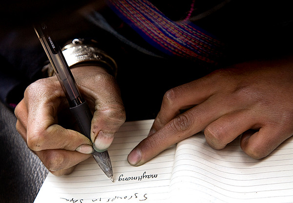 the hands of a hmong village girl, writing her email address.