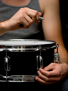 the hands of a multi-instrumentalist, tightening his drum head