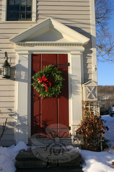 Gold-painted pinecones and a sheer red ribbon are the accents of this pine wreath at 53 Main Street, Newtown.  (Hicks photo)