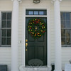 Apples and pears, walnuts and pinecones, and cranberries highlight the festive wreath surrounding the traditional pineapple-shaped door knocker at The Dana-Holcombe House on Main Street.  (Hicks photo)