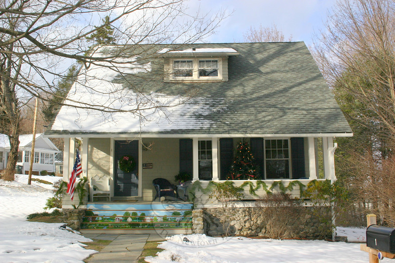 The porch at 1 Schoolhouse Hill Road welcomes guests with a wreath on its front door and a full decorated tree to the right of the door.  (Hicks photo)