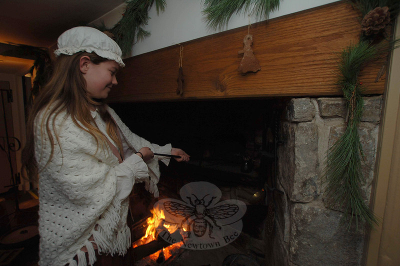 A junior docent demonstrated cooking in a hearth during the open house hosted by Newtown Historical Society on Sunday, December 5.  (Bobowick photo)