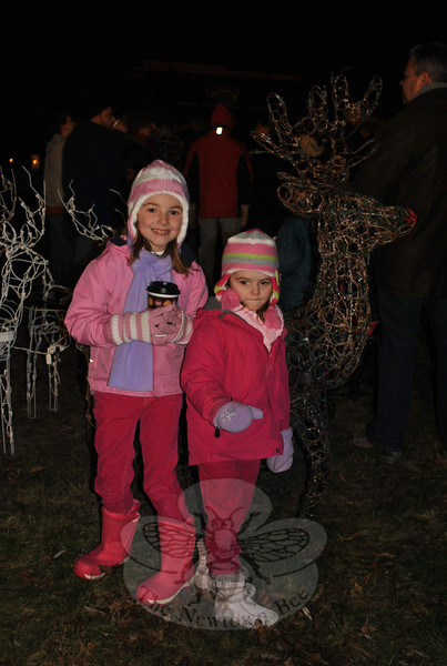 "Leah McCafferty, 7, and sister Abby, 5, visit with Santa's reindeer during the prelighting ""social hour,"" Friday evening, December 3, at the Annual Tree Lighting in Ram Pasture.  (Crevier photo)"