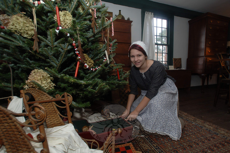 Docent Mairin Hayes helped decorate the tree inside Newtown Historical Society's Matthew Curtiss House on Main Street, which was open for tours on Sunday, December 5. On the tree were simple adornments including dried hydrangea blooms, strands of popcorn and cranberries, homemade gingerbread men, and candy canes.  (Bobowick photo)
