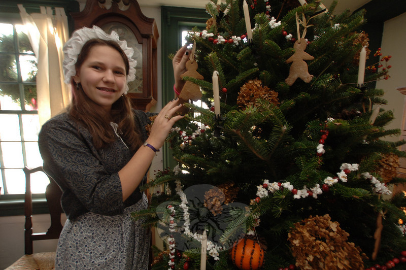 Mairin Hayes had helped decorate The Matthew Curtiss House on Saturday, and then returned during the Holiday Festival to welcome guests to the headquarters of Newtown Historical Society.  (Bobowick photo)