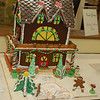 Taking first place in the Family Division of the Holiday Festerival Gingerbread House Contest was this three-story gingerbread mansion created by the Lundquist family, complete with candy cane pillars, octagonal chocolate wafer cookies for shingles, tiny candy snowshoes leaning upon a gingerbread tree, pretzel square balcony railings, and a wood pile of pretzel logs. A Necco wafer pathway led up to the frosted front door, swerving past a gingerbread boy on gingerbread skis, and a gumdrop snowman.  (Crevier photo)
