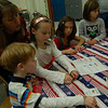 Hawley Elementary School PTA President Marabeth Pereira helped students learn how to fold a flag for Veterans Day on November 11. The flags will be shipped out to soldiers from Fairfield Country fighting in Afghanistan to wear on their shoulders.  (Hallabeck photo)