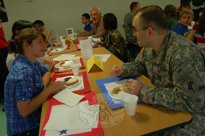 Lieutenant Nenad Filipovic, right, who has served with the Navy and is now with the Army, sits with Newtown Middle School student Raquel Crespo, and other students during the school's Veterans Day breakfast on Wednesday, November 11. (Hallabeck photo)