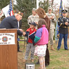 VFW Post 308 member Don Monckton shakes hands with young resident William and his sister Cora Kneen, who approached the podium with their mother Liz on Wednesday. They had taken time to make a collection and present a check to the VFW to help send supplies to active troops.  (Bobowick photo)