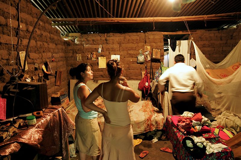 "7/2/2005 --San Salvador, El Salvador --  Imelda Auron and Maria Cebollero (right) look around at their brother, Salvador's, house, while he rushes about, proudly explaining  how he built the structure and has lived there for 17 years. Imelda was particularly horrified at what she perceived as unacceptable poverty and squalor. Maria was less disturbed than her sister, though his living situation did bother her. Salvador has had two trouble marriages, a daughter who drowned at 11 years old, and a daughter who was born deaf. Later, he disclosed to the girls that he has a serious drinking problem. The girls have resolved to send money to their siblings in El Salvador from the US, though they are concerned that Salvador may drink away his portion of the money.<br /> <br /> The sisters were reunited with their three surviving siblings and dozens of nieces, nephews, aunts and uncles on July 2, 2005, after more than 20 years apart.  The girls' parents, who preached Liberation Theology, and two of their older sisters were murdered by the Salvadoran Death Squads on July 31, 1980, which effectively tore the family apart. The sisters' two older brothers joined the Salvadoran Army, and one of them joined the battalion that was notorious in El Salvador for committing the worst atrocities of the civil war (Batallón Atlacatl -- accent over the ""o""). This is tragic and ironic because their murdered parents were on exactly the other side of the conflict than the army and death squads. After their parents' deaths, Maria and Imelda were bounced around among family members for three years before being offered for adoption to the United States by their aunt. They were raised separately and have led very different lives. Imelda is a Montessori school teacher in Boston and Maria is an exotic dancer in Rhode Island. The agency that united them with their family is called Pro-Busqueda, and is headquartered in San Salvador. Story by Yvonne Abraham; Photo by Dina"