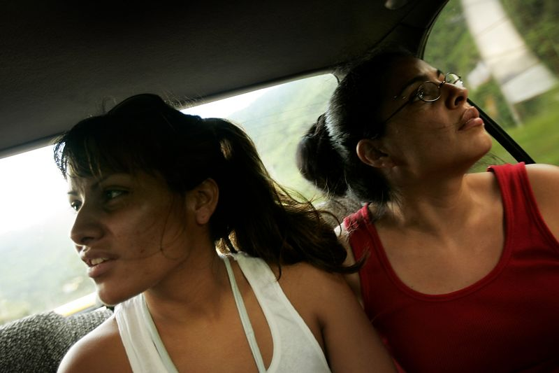7/1/2005 -- En route from the El Salvador Airport to San Salvador, El Salvador --  Maria (left) Cebollero (cq) and Imelda Auron are mesmerized by the abundant green landscape and soaring hills as their cab drove from the El Salvador airport to their guest house in San Salvador. Neither of them had been to the country of their birth since they were adopted out to the United States more than twenty years earlier. Story by Yvonne Abraham; Photo by Dina Rudick, Boston Globe Staff