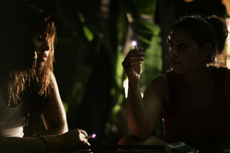 7/1/2005 --San Salvador, El Salvador -- Maria Cebollero (cq, left) and her sister, Imelda Auron smoke cigarettes and share their anxiety in the back patio of their guest house in San Salvador. The next morning, they planned to travel to the Salvadoran countryside to meet their birth family, whom they've not seen in more than twenty years. Story by Yvonne Abraham; Photo by Dina Rudick, Boston Globe Staff