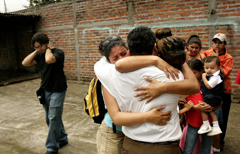 "7/2/2005 --San Salvador, El Salvador --  This is the first two minutes that Maria Cebollero (right) and Imelda Auron were reunited with their three surviving siblings and dozens of nieces, nephews, aunts and uncles. (They are hugging Salvador, the eldest brother. The man to the left in the picture is psychologist Marco Perez, who guided the sisters through the reunification.) The girls' parents, who preached Liberation Theology, and two of their older sisters were murdered by the Salvadoran Death Squads on July 31, 1980, which effectively tore the family apart. The sisters' two older brothers joined the Salvadoran Army, and one of them joined the battalion that was notorious in El Salvador for committing the worst atrocities of the civil war (Batallón Atlacatl -- accent over the ""o""). This is tragic and ironic because their murdered parents were on exactly the other side of the conflict than the army and death squads. After their parents' deaths, Maria and Imelda were bounced around among family members for three years before being offered for adoption to the United States by their aunt. They were raised separately and have led very different lives. Imelda is a Montessori school teacher in Boston and Maria is an exotic dancer in Rhode Island. The agency that united them with their family is called Pro-Busqueda, and is headquartered in San Salvador.  Story by Yvonne Abraham; Photo by Dina Rudick, Boston Globe Staff"