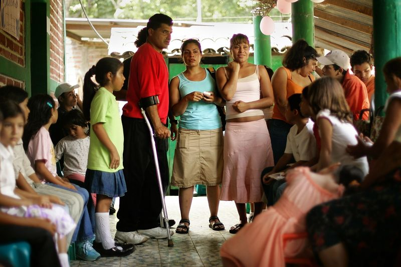 "7/2/2005 --San Salvador, El Salvador --  Maria Cebollero (right) and Imelda Auron try to take in the faces and names of relatives they know only through vague memories or scraps of stories. They were reunited with their three surviving siblings and dozens of nieces, nephews, aunts and uncles on July 2, 2005 after more than twenty years apart. The girls' parents, who preached Liberation Theology, and two of their older sisters were murdered by the Salvadoran Death Squads on July 31, 1980, which effectively tore the family apart. The sisters' two older brothers joined the Salvadoran Army, and one of them joined the battalion that was notorious in El Salvador for committing the worst atrocities of the civil war (Batallón Atlacatl -- accent over the ""o""). This is tragic and ironic because their murdered parents were on exactly the other side of the conflict than the army and death squads. After their parents' deaths, Maria and Imelda were bounced around among family members for three years before being offered for adoption to the United States by their aunt. They were raised separately and have led very different lives. Imelda is a Montessori school teacher in Boston and Maria is an exotic dancer in Rhode Island. The agency that united them with their family is called Pro-Busqueda, and is headquartered in San Salvador. Story by Yvonne Abraham; Photo by Dina Rudick, Boston Globe Staff"