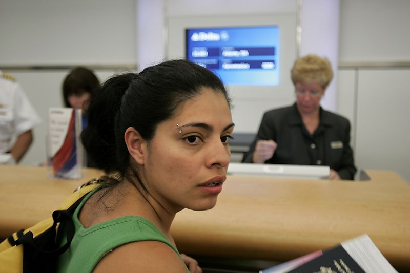 6/30/2005 -- Boston Logan International Airport --  Barely an hour after she awoke to realize she had slept through her alarm, Imelda barely makes it to the gate in time to board her 6 am flight to El Salvador (connecting in Atlanta) on Thursday morning, June 30. This marked the beginning of her journey home to meet her birth family in El Salvador. Story by Yvonne Abraham; Photo by Dina Rudick, Boston Globe Staff