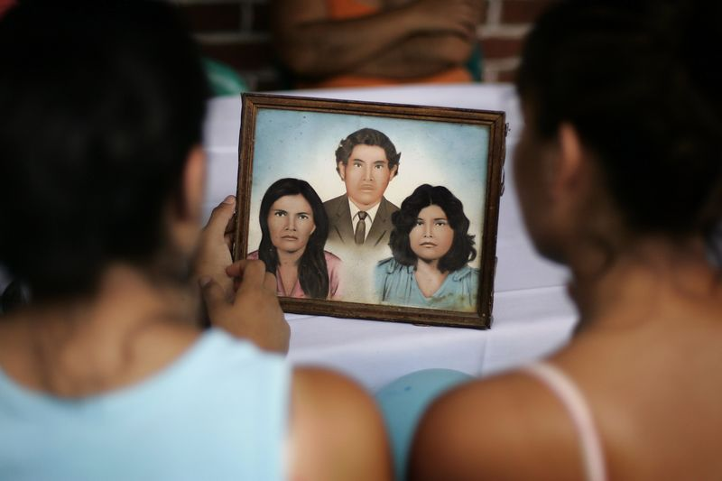 "7/2/2005 --San Salvador, El Salvador -- In this picture, Imelda (left) and Maria look at a picture of their parents and sister.  Maria Cebollero and her sister Imelda Auron were reunited with their three surviving siblings and dozens of nieces, nephews, aunts and uncles on July 2, 2005 after more than twenty years apart. The girls' parents, who preached Liberation Theology, and two of their older sisters were murdered by the Salvadoran Death Squads on July 31, 1980, which effectively tore the family apart. The sisters' two older brothers joined the Salvadoran Army, and one of them joined the battalion that was notorious in El Salvador for committing the worst atrocities of the civil war (Batallón Atlacatl -- accent over the ""o""). This is tragic and ironic because their murdered parents were on exactly the other side of the conflict than the army and death squads. After their parents' deaths, Maria and Imelda were bounced around among family members for three years before being offered for adoption to the United States by their aunt. They were raised separately and have led very different lives. Imelda is a Montessori school teacher in Boston and Maria is an exotic dancer in Rhode Island. The agency that united them with their family is called Pro-Busqueda, and is headquartered in San Salvador. Story by Yvonne Abraham; Photo by Dina Rudick, Boston Globe Staff"