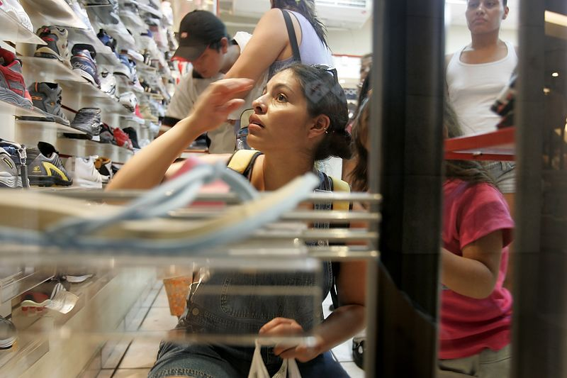 7/3/2005 --San Salvador, El Salvador --  Imelda Auron (foreground) and her sister Maria Cebollero took their family to the Metro Centro mall in San Salvador on Sunday morning, the day after they were reunited after more than 20 years apart. The girls were apprehensive about how to respond to and treat their family, who were effectively strangers. The young girls (their nieces) delighted in the coin-operated rides in the atrium. Imelda bought some of the children shoes, which caused minor conflict as some of the siblings pointed out how certain children received gifts while others received none. After several hours of shopping and eating at Pizza Hut, the girls were ready to get out of the situation as quickly as possible (especially Imelda, who made up an excuse to leave). Neither of the girls feels close the siblings, though they feel obligated to care for them now. Both girls are glad they now know their family. Story by Yvonne Abraham; Photo by Dina Rudick, Boston Globe Staff