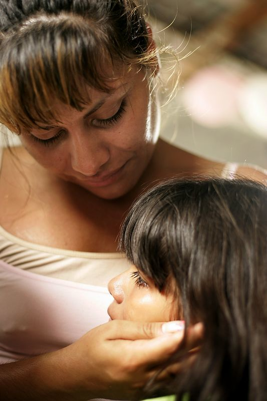 """7/2/2005 --San Salvador, El Salvador --  Maria Cebollero meets her neice, Sara, for the first time on July 2, 2005. Maria and her sister, Imelda Auron, were reunited with their three surviving siblings and dozens of nieces, nephews, aunts and uncles. The girls' parents, who preached Liberation Theology, and two of their older sisters were murdered by the Salvadoran Death Squads on July 31, 1980, which effectively tore the family apart. The sisters' two older brothers joined the Salvadoran Army, and one of them joined the battalion that was notorious in El Salvador for committing the worst atrocities of the civil war (Batallón Atlacatl -- accent over the """"o""""). This is tragic and ironic because their murdered parents were on exactly the other side of the conflict than the army and death squads. After their parents' deaths, Maria and Imelda were bounced around among family members for three years before being offered for adoption to the United States by their aunt. They were raised separately and have led very different lives. Imelda is a Montessori school teacher in Boston and Maria is an exotic dancer in Rhode Island. The agency that united them with their family is called Pro-Busqueda, and is headquartered in San Salvador. Story by Yvonne Abraham; Photo by Dina Rudick, Boston Globe Staff"""