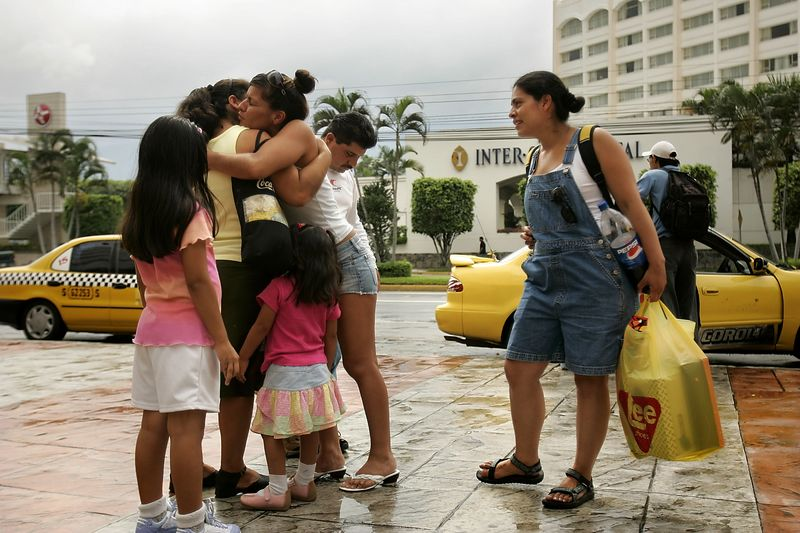 7/3/2005 --San Salvador, El Salvador --  Imelda Auron (left) and her sister Maria Cebollero hugging) took their family to the Metro Centro mall in San Salvador on Sunday morning, the day after they were reunited after more than 20 years apart. The girls were apprehensive about how to respond to and treat their family, who were effectively strangers. The young girls (their nieces) delighted in the coin-operated rides in the atrium. Imelda bought some of the children shoes, which caused minor conflict as some of the siblings pointed out how certain children received gifts while others received none. After several hours of shopping and eating at Pizza Hut, the girls were ready to get out of the situation as quickly as possible (especially Imelda, who made up an excuse to leave). Neither of the girls feels close the siblings, though they feel obligated to care for them now. Both girls are glad they now know their family. Story by Yvonne Abraham; Photo by Dina Rudick, Boston Globe Staff
