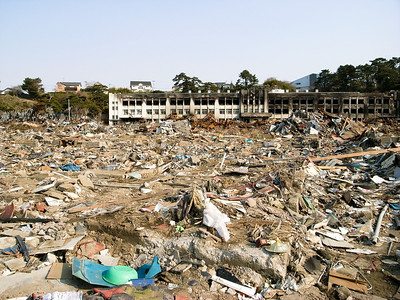 An elemantary school that was burned when dozens of cars swept by the tsunami wave crashed against it and caught up in flames.