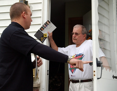Dan Strohsack, left, respresenting the Lorain County Sheriff's Office and Lorain County Deputies Assoc., talks to Roger Vanek at his home in Elyria about Issue 4 on Oct. 8.    Steve Manheim/CT