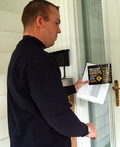 Dan Strohsack, respresenting the Lorain County Sheriff's Office and Lorain County Deputies Assoc., places information on Issue 4 at a home in Elyria on Oct. 8.    Steve Manheim/CT