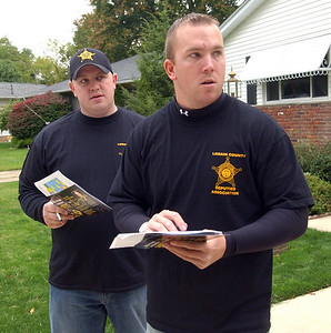 Ryan Sayers, left, and Dan Strohsack, both representing the Lorain County Sheriff's office and Lorain County Deputies Assoc., go door-to-door in Elyria to gain support for Issue 4 on Oct. 8.   Steve Manheim/CT