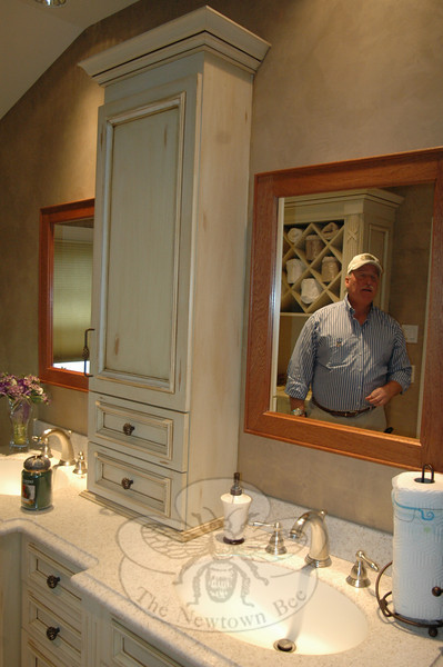 Architectural Kitchens & Baths manager Robert Bishop, in mirror, points out one of the custom made, distressed wood cabinets manufactured in-house and installed at the company's South Main Street location.  (Voket photo)