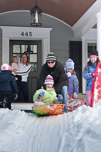 (1) Pslip Slug #: (Pending); (2) Ridgewood, NJ; (3) 01/12/2011; (4) Ridgewood Responds to Another Snow Storm; (5) Ellen McKenna gives Courtney a push while Courtney and Grace wait their turn on 1/12/2011; (6) W.H. Grae for the Ridgewood News.