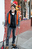 """Buster has been a sweeper on Haight Street for 20 years.  He remarks, """"Panhandling is a tradition on Haight Street.   Peace-love is coming back.""""   The grocer (who declined to be identified) at the Organic Produce Market said, """"I've dealt with these street people for 29 years.   You have to know how to treat people.""""   Photo taken in the early morning on Haight Street, San Francisco, California on October 26, 2010 by Alex Woo."""