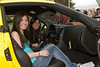 Adalyn Naka and Pamela Bravo sit in the yellow Corvette
