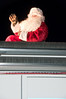 Santa waves from the top of his fire engine.