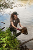 Erin Winograd picks up trash along the Anacostia River bank.