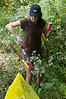 Terri Strassburger retrieves trash from the undergrowth along the bank of the Potomac.