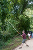 John Hammer uses a pole saw and clippers to remove overhanging branches from the path.