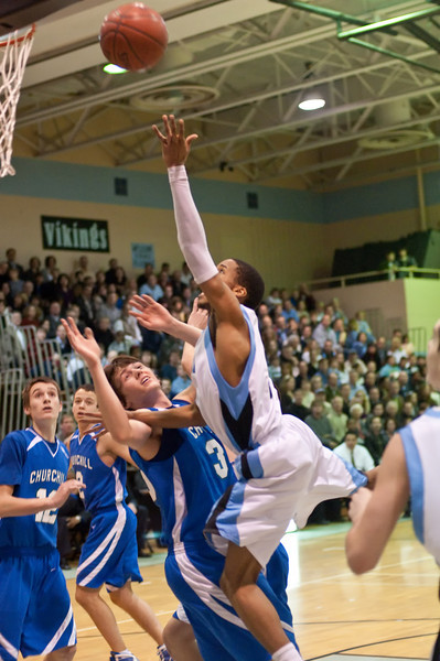 Demetrius Cook of Whitman drives to the basket as Churchill's Kyle Edwards defends.