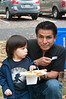 Julio (3 years old) and his father Alfredo Cupe sample the food at the picnic.