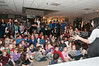 An attentive crowd listens to the story of Chanukah as told by Joelle Kelenson (Coordinator of School Age Services).