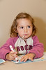 Two year old Nicole Subiela does some coloring while waiting for the candle-lighting to start.