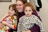 Kay Lee Fellner, 6 years old, her mother Nechama Fellner, nad 2 year old Ross Fellner listen to the Chanukah story.