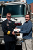 """Chief James Seavey Sr. receives a check from Matthew Stuart of Potomac Estate Jewellers.  The Potomac Chamber of Comerce sponsored a """"gold exchange"""" in January and Matthew Stuart pledged a portion of the proceeds to local charities."""