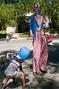 A boy pciks up candy thrown from a car as a tall Uncle Sam observes..