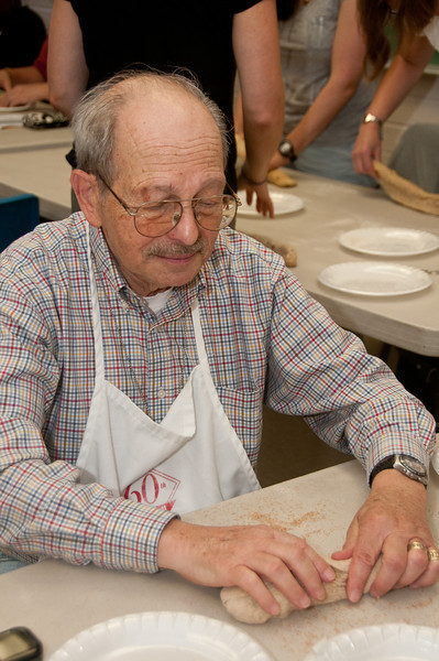 Jack Klass of Silver Spring rolls the dough into a thin cylinder so that it can be coiled into a round loaf that is traditional for Rosh Hashanah.