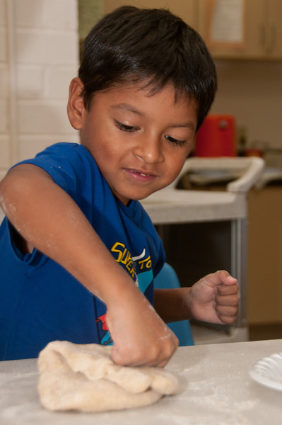 Diego Meneses, 4 years old from Germantown, is having a good time kneeding dough.
