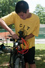 "Chris Hallock (14 years old, incoming Churchill freshman) disassembles a bike for shipping by ""Bikes for the World""."