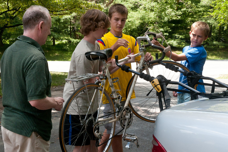 Andrew Greenberg (14 years old), Conor Quigley (14 years old) and Jack Quigley (12 years old) remove a dontated bike from a car rack.