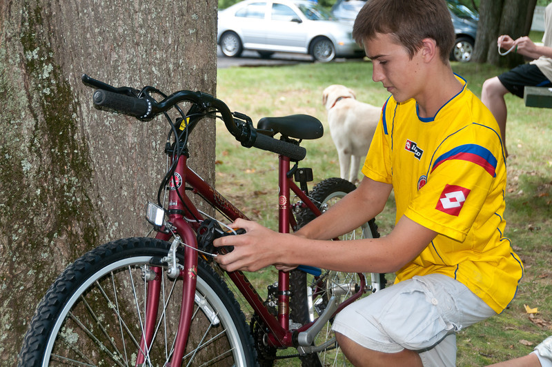 "Event organizer Conor Quigley (14 years old, incoming Churchill HS freshman) begins to break down a donated bike for pcikup by the ""Bikes for the World"" truck."