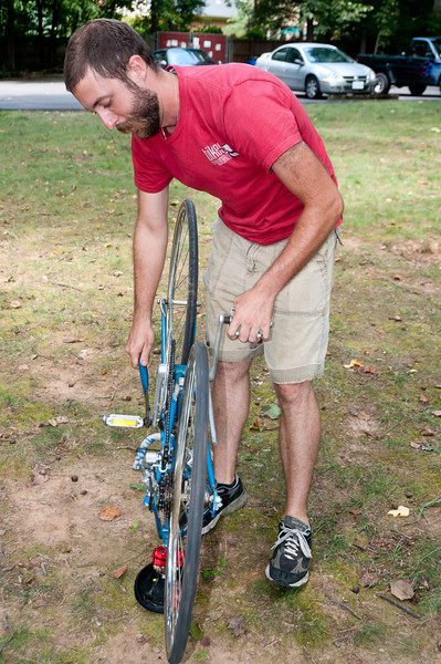 Nick Colombo, Operations Manager for Bikes for the World, works on removing a pedal from a donated bike.
