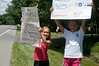Claire Quigley (9 years old, Potomac El.) and Eliza Asbury (10 years old, Potomac EL) hold up signs to advertise the Bikes for the World collection and the accompanying bake sale.